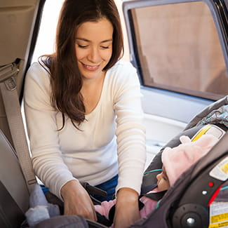 mother putting baby into car seat Denver Health