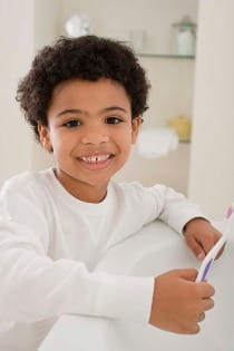 happy kid brushing his teeth image